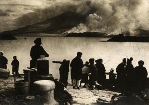 Vulkaanuitbarsting Sakoeragima / Sakurajima 1914 : Bewoners van het eiland Sakoeragima / Sakurajima zijn naar de stad Kagoshima gevlucht, aan de overkant van de zeestraat, en zien enorme wolken as rond de uitbarstende vulkaan. Japan, 1914.